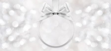 silver wedding anniversary: silver shiny ribbon bow on blurred background Stock Photo