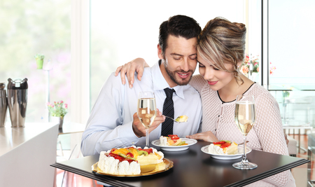 people eating restaurant: happy couple at the bar with wine and fruit cake, love concept