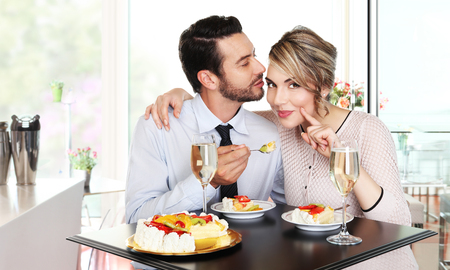 couple dating: happy couple at the bar with sparkling wine and cake, love concept Stock Photo
