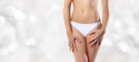 young woman panties: woman hands resting on the thighs isolated on blurred lights background