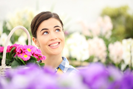 beautiful smile: springtime woman smiling in garden and looking up with white wicker basket flowers of purple primroses
