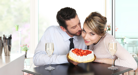 pleasantness: happy couple at the bar with sparkling wine and cake, love concept Stock Photo