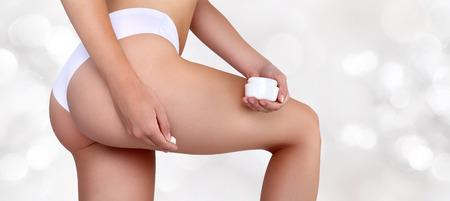 stretch: woman hands applying moisturizer cream on thigh