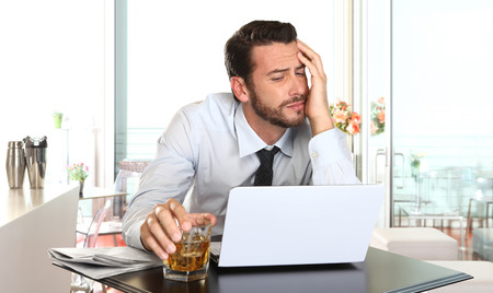 burnout: worried and tired businessman in crisis working on computer laptop at bar table in stress under pressure facing work problems
