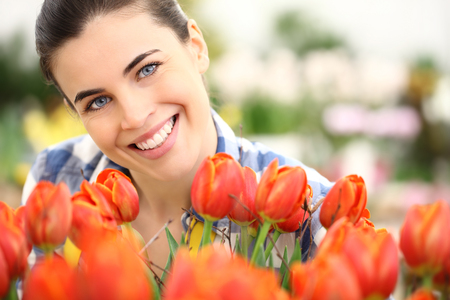 beautiful flowers: springtime, smiling woman  in garden with flowers tulips Stock Photo