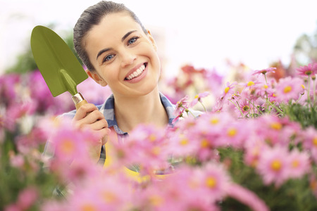 smiling woman in a greenhouse: springtime woman smiling in garden with tools in hand