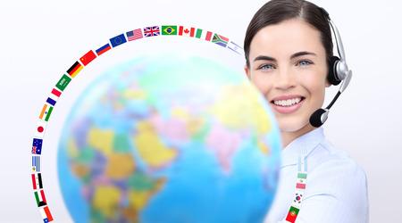 idiomas: mujer de operador de servicio al cliente con auriculares sonriente, globo, banderas internacionales, póngase en contacto con nosotros concepto