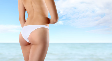 buttocks and legs of slim woman isolated on sea background