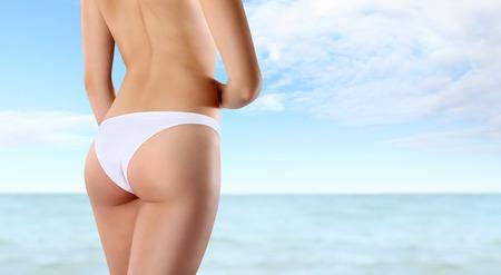 hintern: Gesäß und Beine der schlanke Frau auf dem Meer Hintergrund isoliert