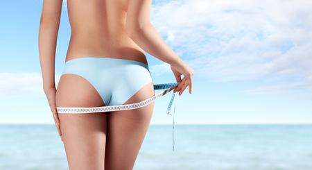 nalga: la mano con el metro, las nalgas y las piernas de la mujer delgada aislada en el fondo marino durante el verano