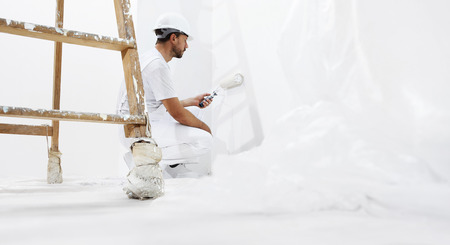 painting and decorating: painter man at work with a paint roller on the white wall