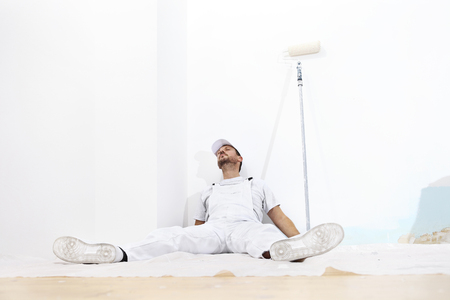 downtime: painter man tired, lying on the floor, isolated on white wall
