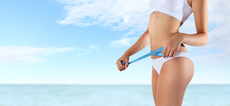 summer diet: woman holding blue meter with hands near waistline, isolated on sky and sea  background Stock Photo