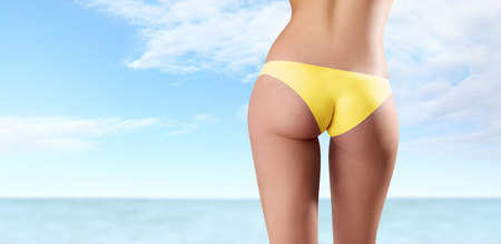 nalga: Detrás de la mujer en bikini amarillo aislado en el mar y el cielo de fondo