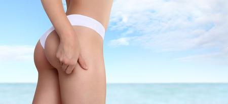 mujer celulitis: La mujer pellizca su muslo para controlar la celulitis, aislada en el mar y el cielo de fondo