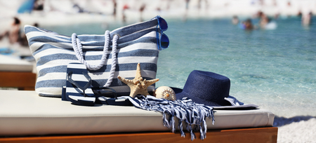 bag with blue hat, sandals, starfish, sea shell and towel on the beach
