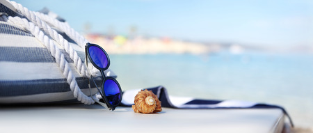 white towel: bag on the beach with blue sunglasses, shells and towel Stock Photo