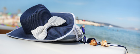 blue hat on the beach with bag, sunglasses, shells and towel