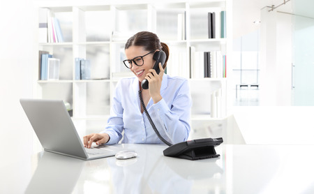 mujer alegre: mujer sonriente en la Oficina en el escritorio con el ordenador, hablando por teléfono