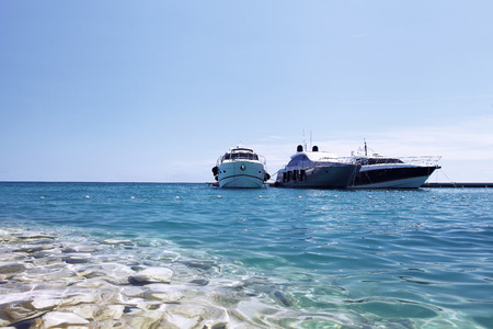 millonario: luxury boats on the beach, in blue sea and blue sky