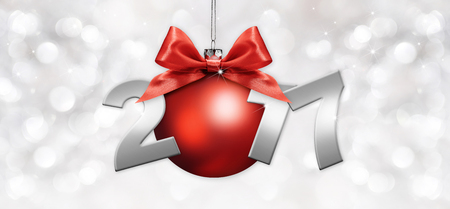 new year tree: red christmas ball with red ribbon bow and 2017 text on silver blurred lights background Stock Photo