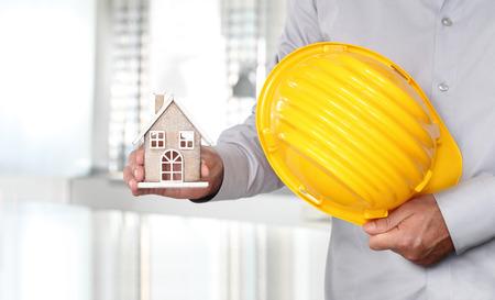 Hände mit Haus und Arbeitshelm Sicherheit Baukonzept Standard-Bild