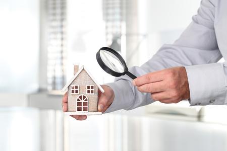 Handen met huis, vergrootglas, zoeken home-concept