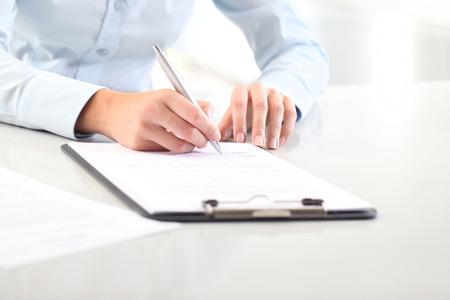 De handen die van de vrouw op blad van document in een klembord en een pen, op bureau schrijven Stockfoto