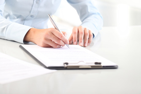 Woman's hands writing on sheet of paper in a clipboard and a pen, on desk