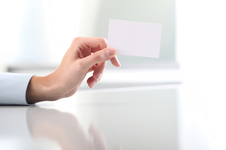 hand hold: woman Hand hold blank business card, on desk Stock Photo