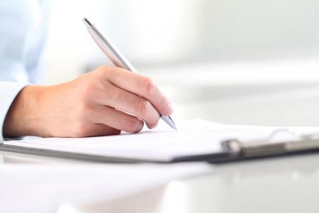 De handen die van de vrouw op blad van document in een klembord en een pen schrijven; geïsoleerd op een bureau Stockfoto - 63956737