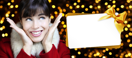 woman with christmas gift card in lights background