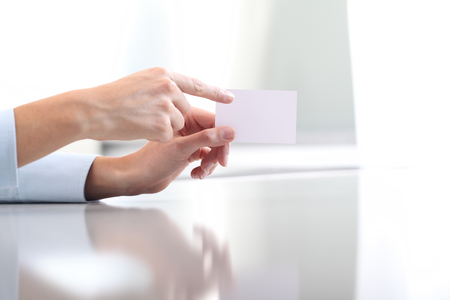 take a note: Hand hold blank business card, on desk top