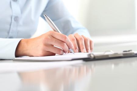 portapapeles: Manos de la mujer joven que escribe en la hoja de un bloc de notas con un bolígrafo; aislado en el escritorio