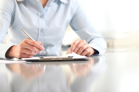 책상에 고립 된 클립 보드에 쓰는 여자 손, 스톡 콘텐츠
