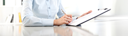 woman hands writing on clipboard, isolated on desk panoramic Standard-Bild