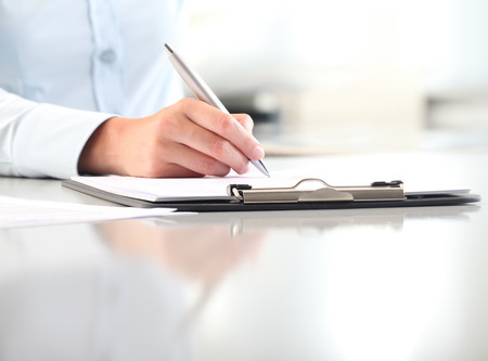 woman hands writing on clipboard with a pen, isolated on desk office Stock Photo