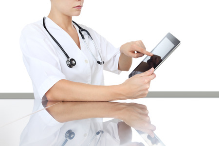 doctor at desk touch tablet in medical office remot control device, concept Stock Photo