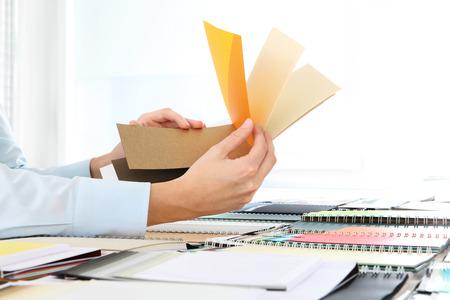 sample: hands choosing a color from the sampler on desk