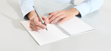 writing book: female hands with pen writing on notebook  on desk