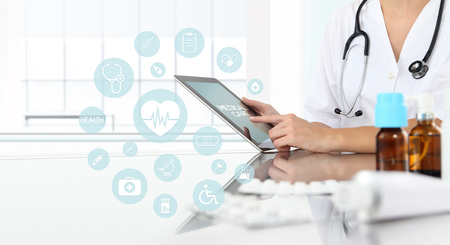 doctor using tablet with icons in medical office with drugs on clinic desk