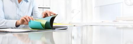 手のオフィス デスクの上でサンプラーから色を選択します。