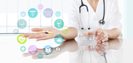 Doctor with pills in hand and colored icons. medical concept