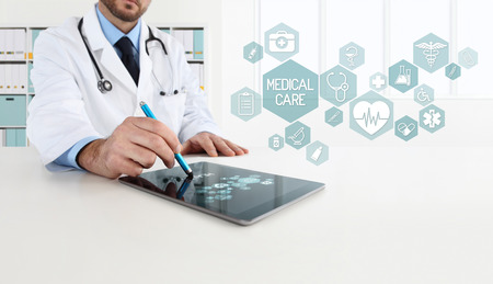 doctor uses the tablet with blue icons, in office desk Stok Fotoğraf - 69675827