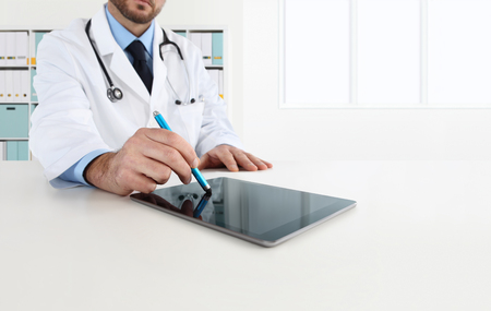 doctor using tablet on desk in office