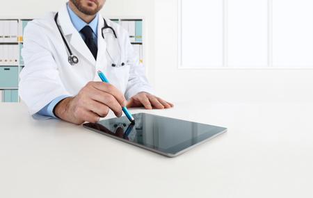 doctor using tablet on desk in office