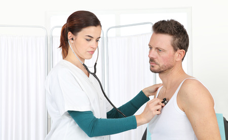stress test: Doctor examining patient with stethoscope in medical office Stock Photo