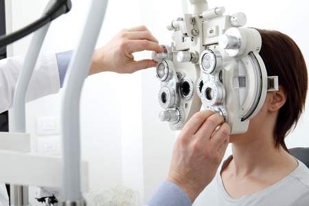 woman doing eyesight measurement with optical phoropter. Banque d'images