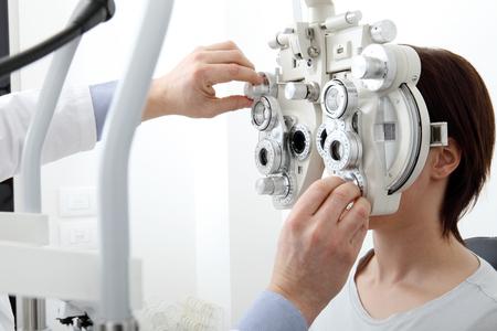 vrouw die zicht meting met optische phoropter.