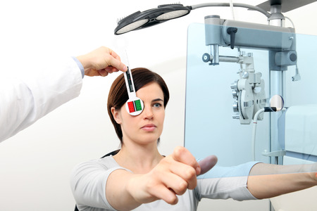 optometrist optician doctor examines eyesight of woman patient in eye ophthalmological clinic. Stock Photo
